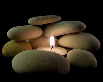 Mit ganz einfachen Tricks kann man den Wellnesscharakter des Badezimmers hervorheben, zum Beispiel mit aufeinander gelegten Steinen und einer Kerze dazwischen, wie es das Bild zeigt.